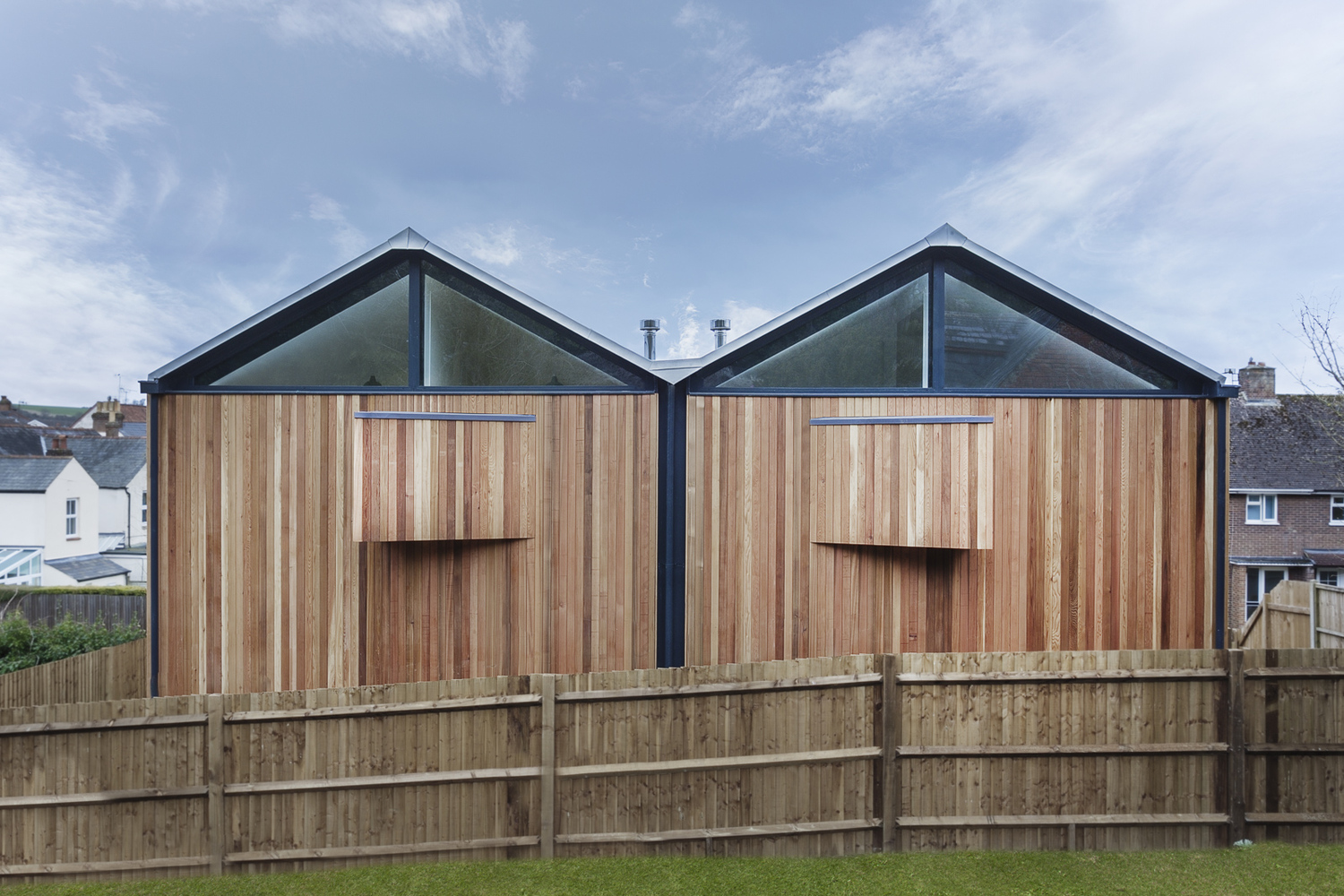 Two contemporary timber pods on top of a dark monolithic for Modern zinc houses