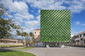 A monumental entrance of deep-green, glazed terra cotta tiles