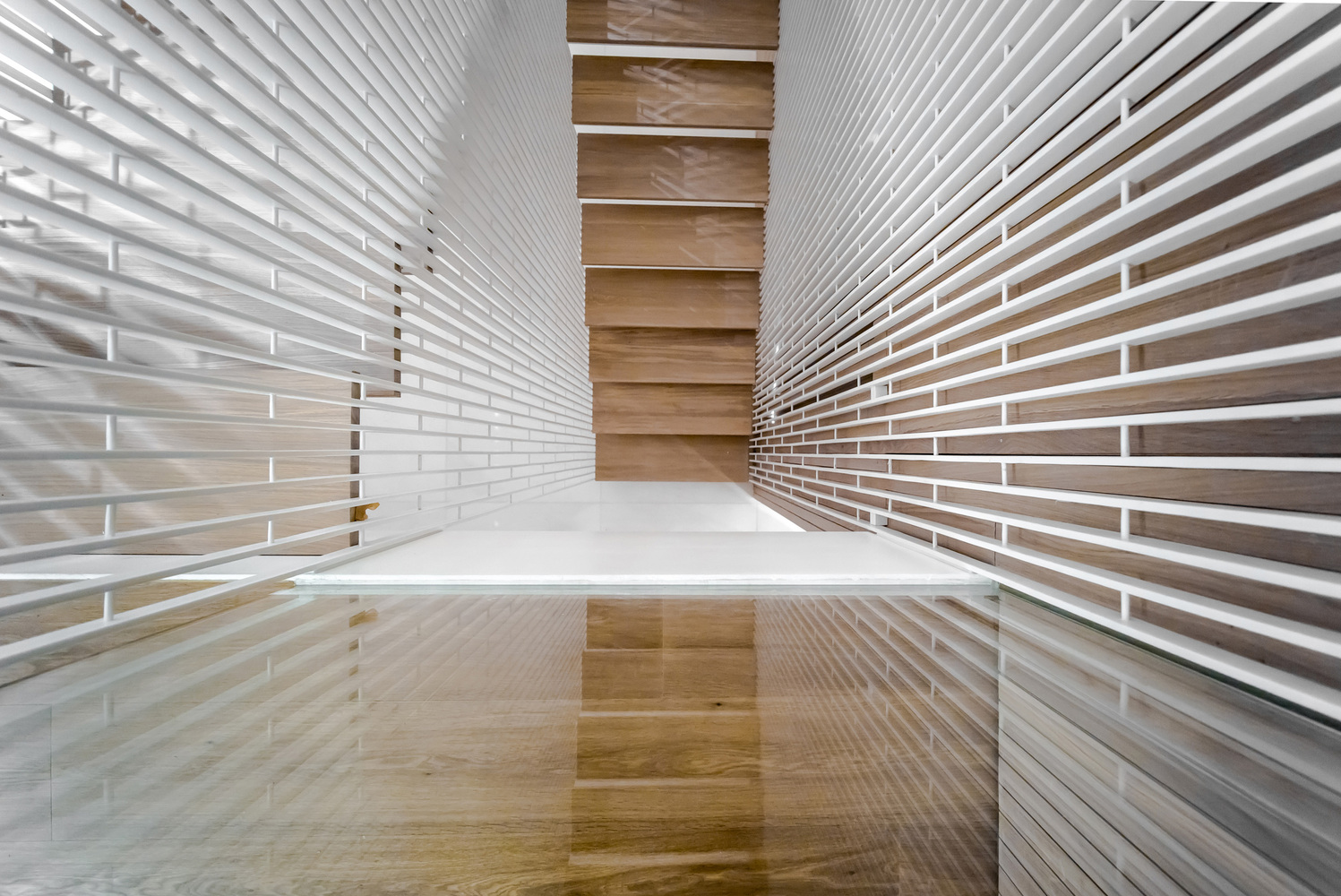 A floating stair and a cladded wooden skin define Wood architecture definition